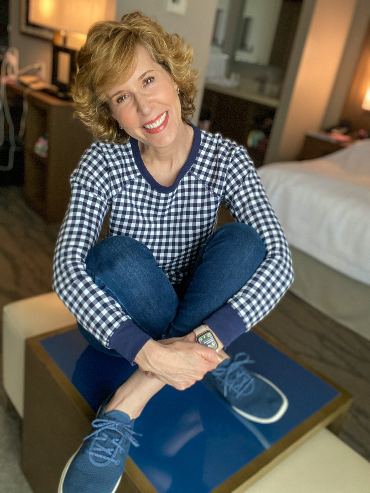 woman in navy blue gingham sweatshirt and jeans sitting on a table