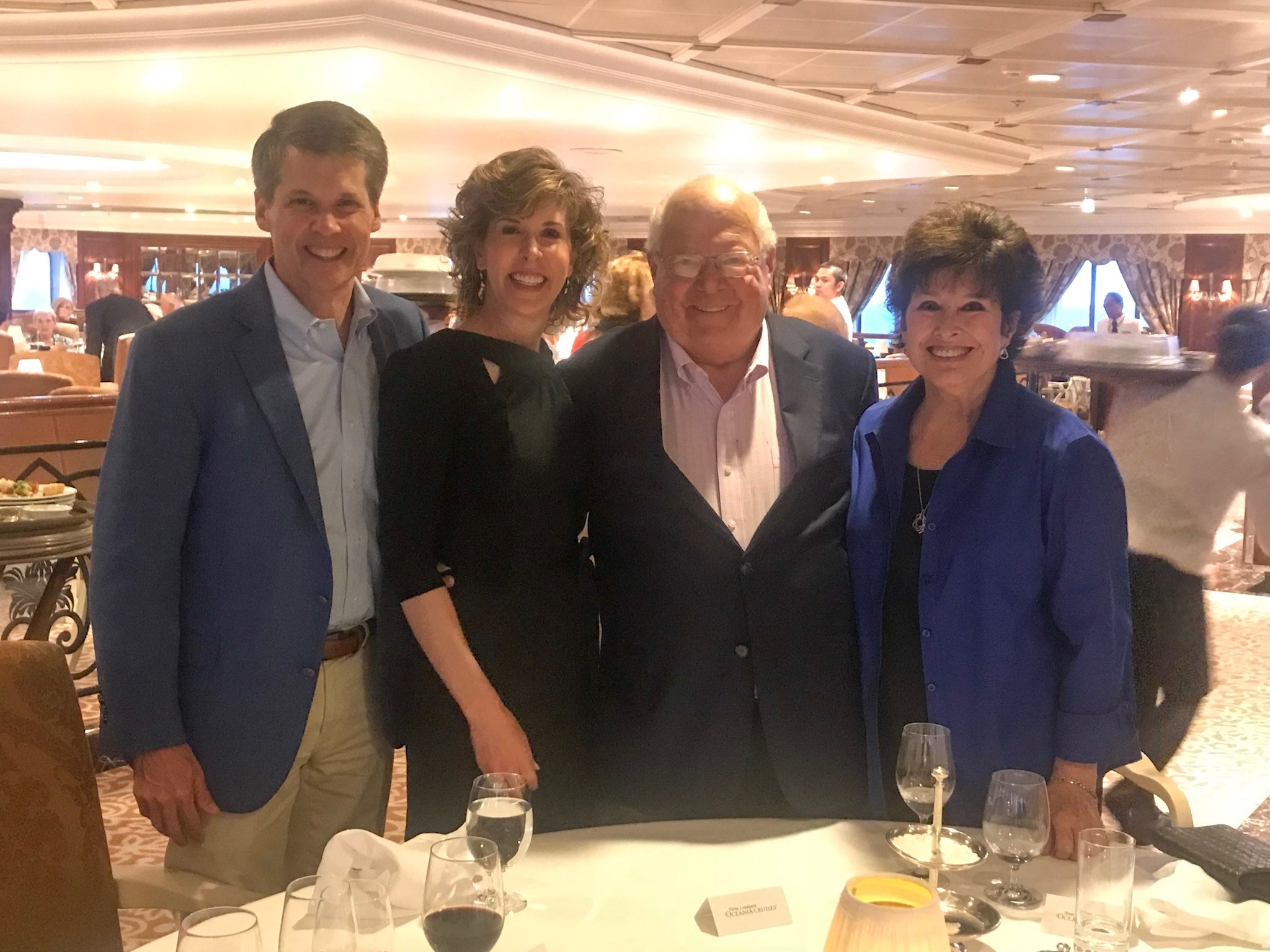 four people posing in the dining room on a cruise ship