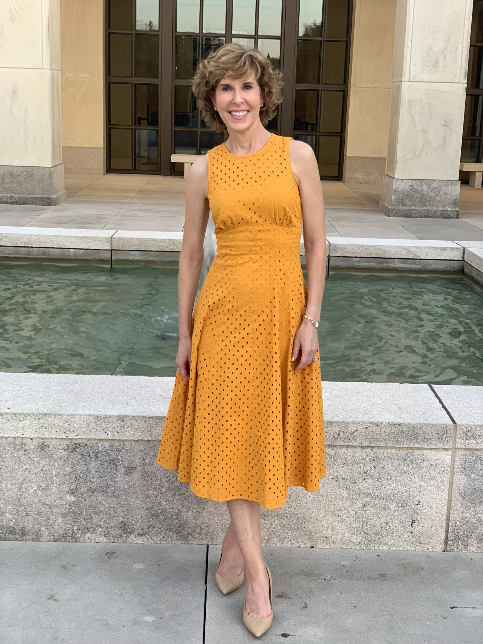 woman in gold dress in front of fountain