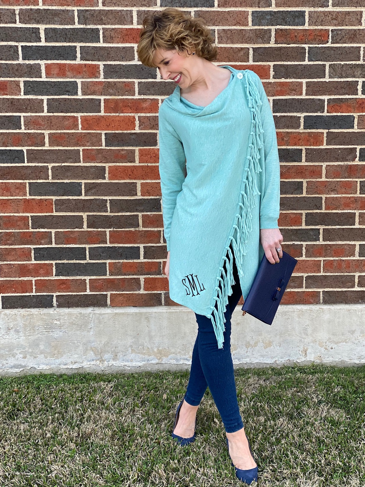 woman wearing 2020 spring style trends in seafoam green wrap cardigan and jeans standing in front of a brick wall