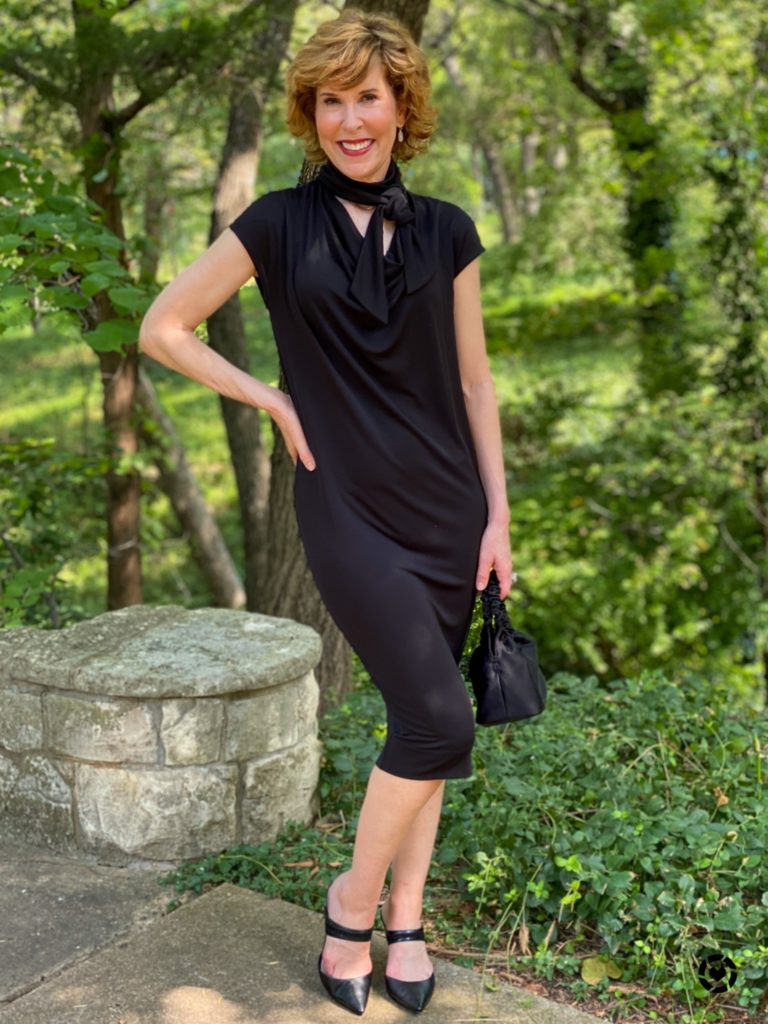 empty nester woman wearing chico's black label cap sleeve dress standing near a stone pedestal in the woods