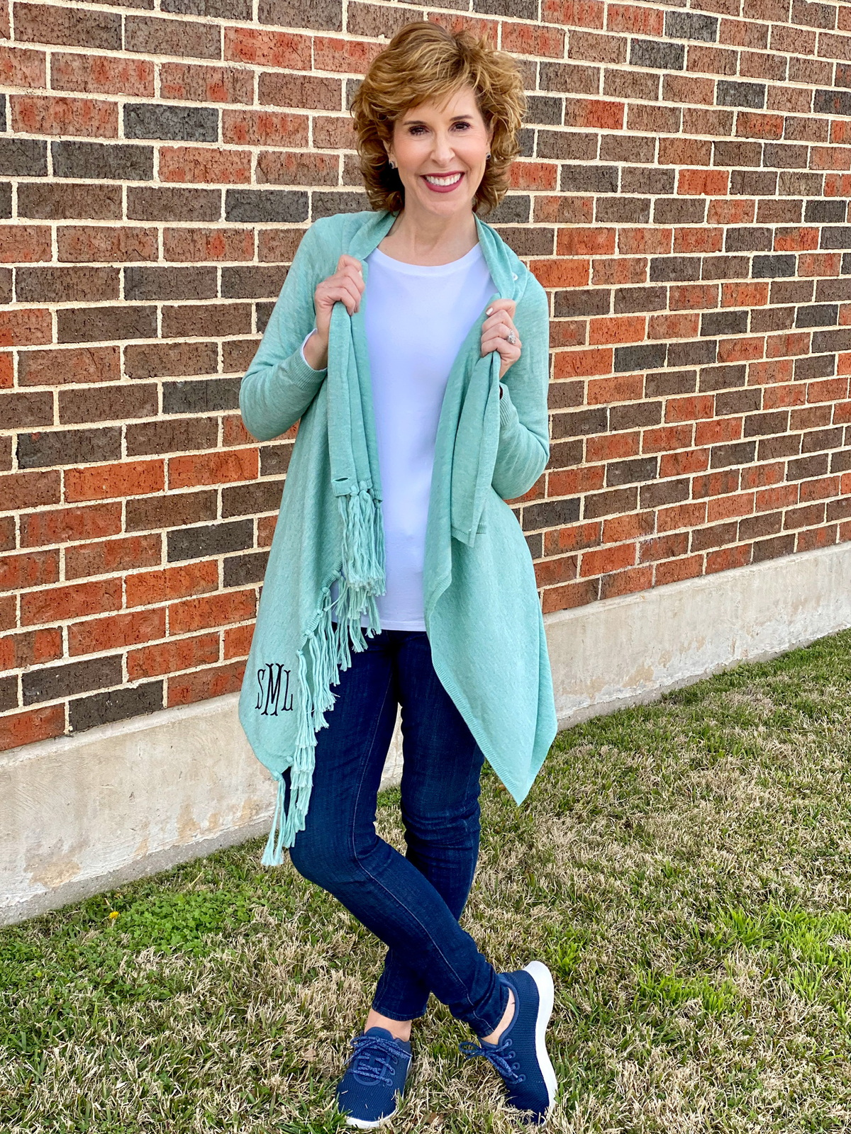 woman wearing seafoam green wrap cardigan and jeans standing in front of a brick wall