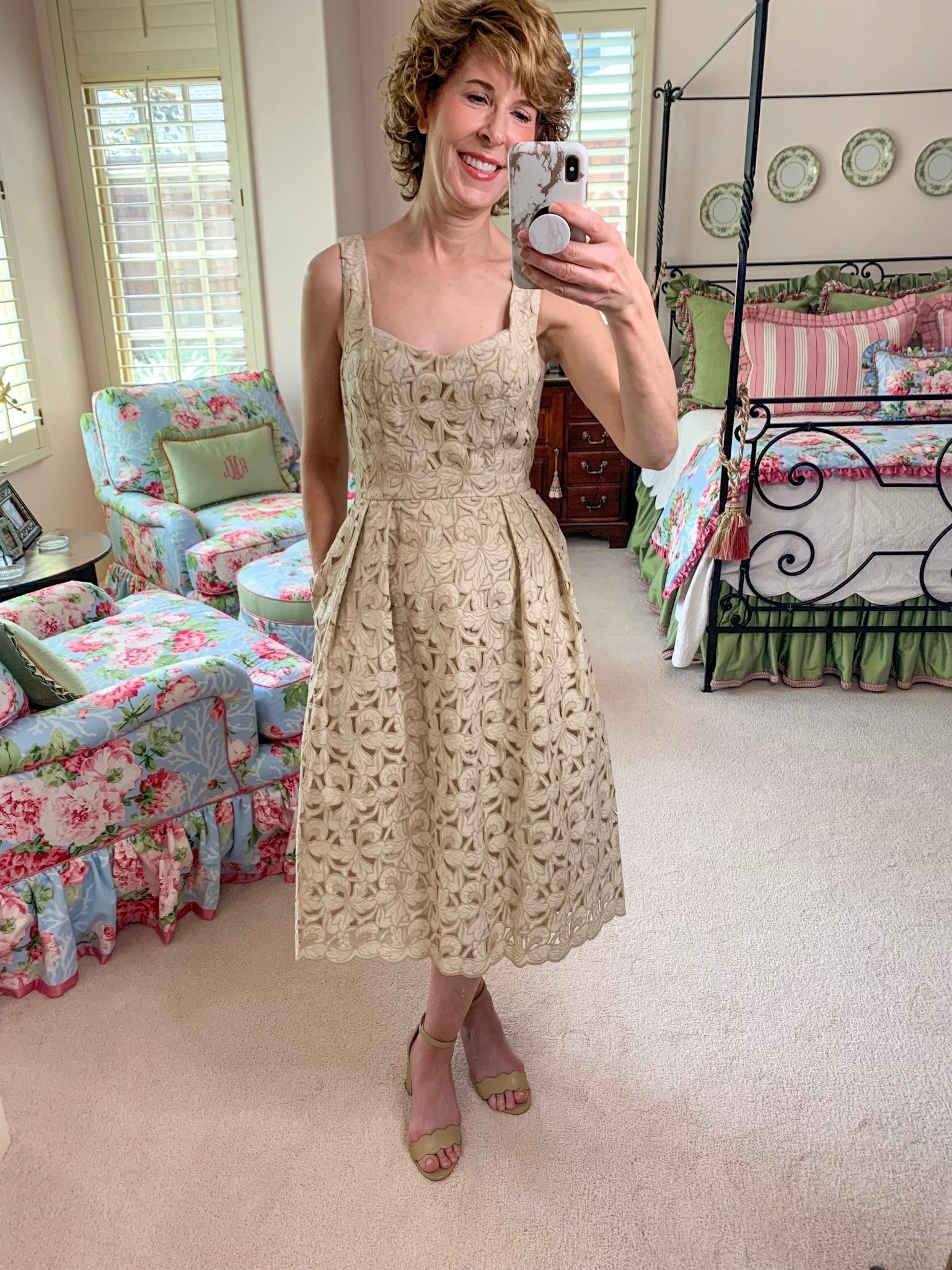 mirror selfie of woman in neutral lace dress