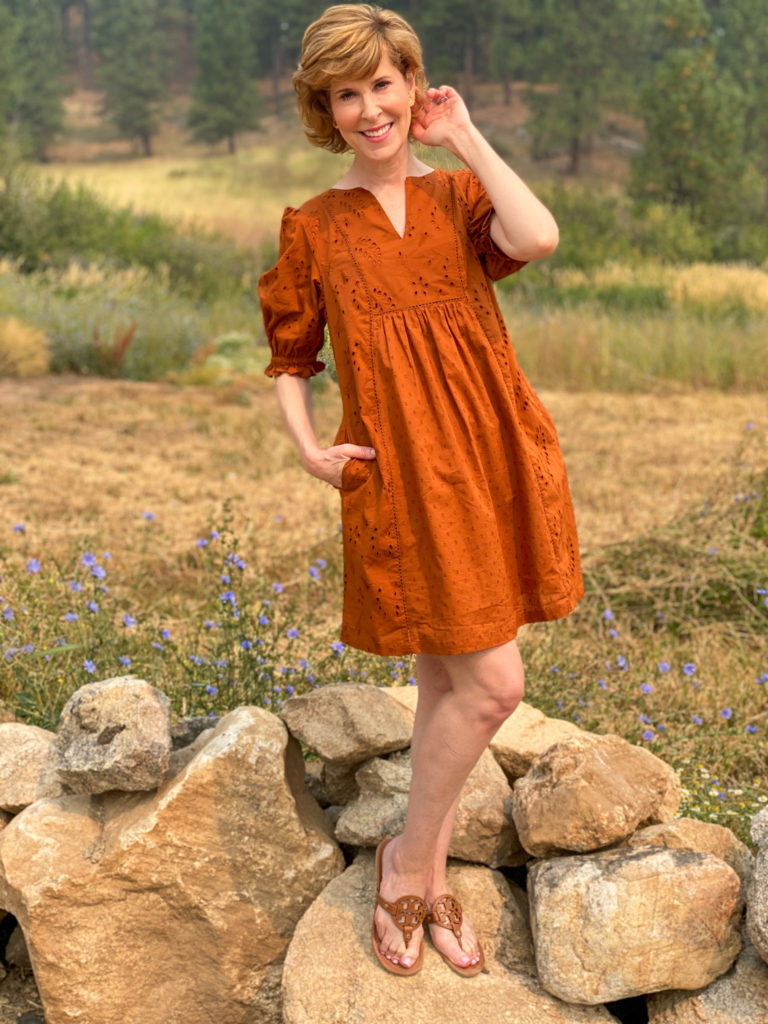 woman wearing light burnt orange dress standing on rocks near mountains