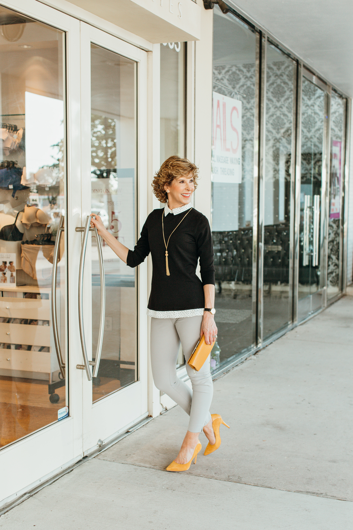 woman standing at door of a shop wearing one of the 2019 fall trends