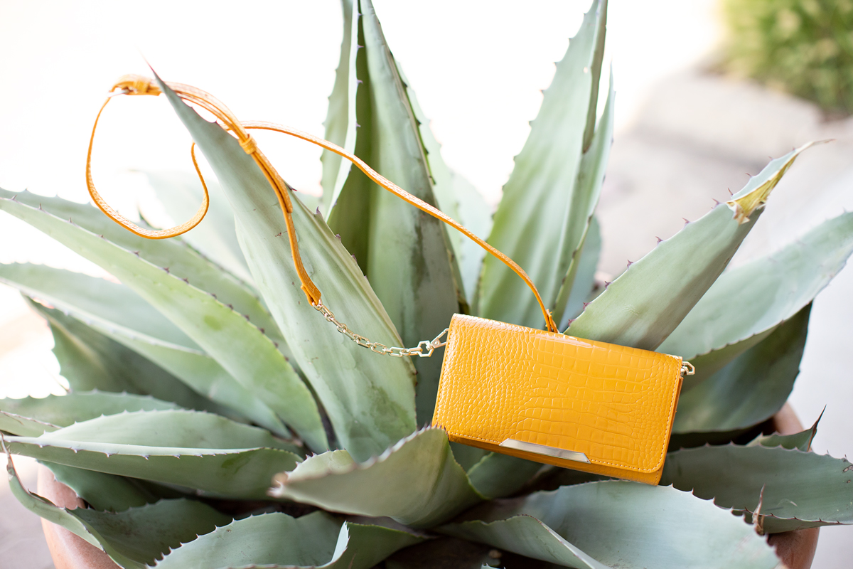 yellow handbag sitting among the leaves of a plant example of 2019 fall shoe & accessory trends
