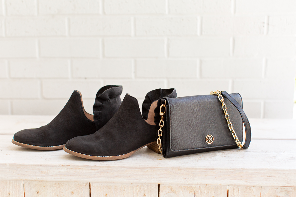black booties and clutch sitting on a bench