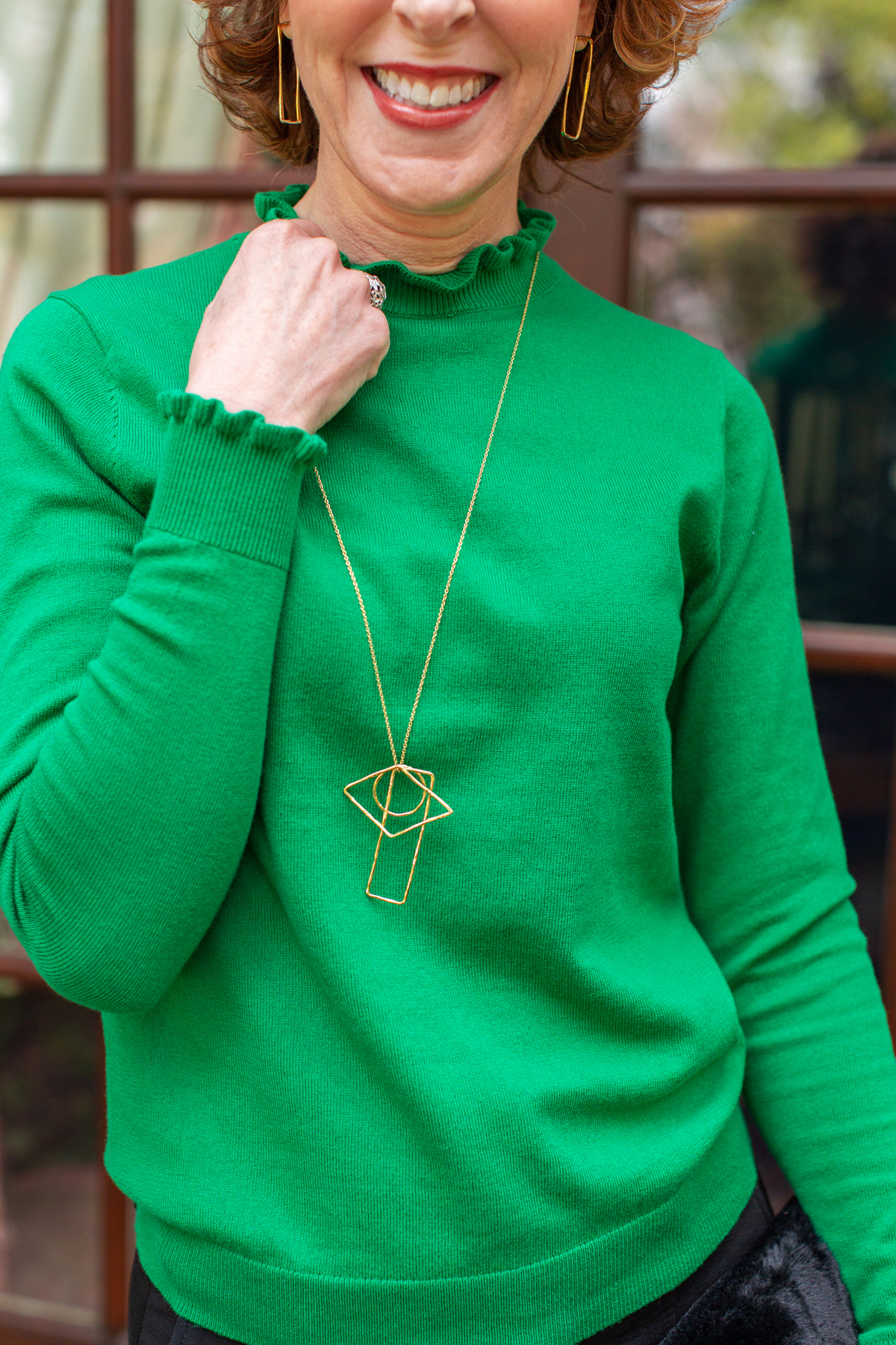 woman in green sweater with neck ruffle demonstrating a spring & summer style trend