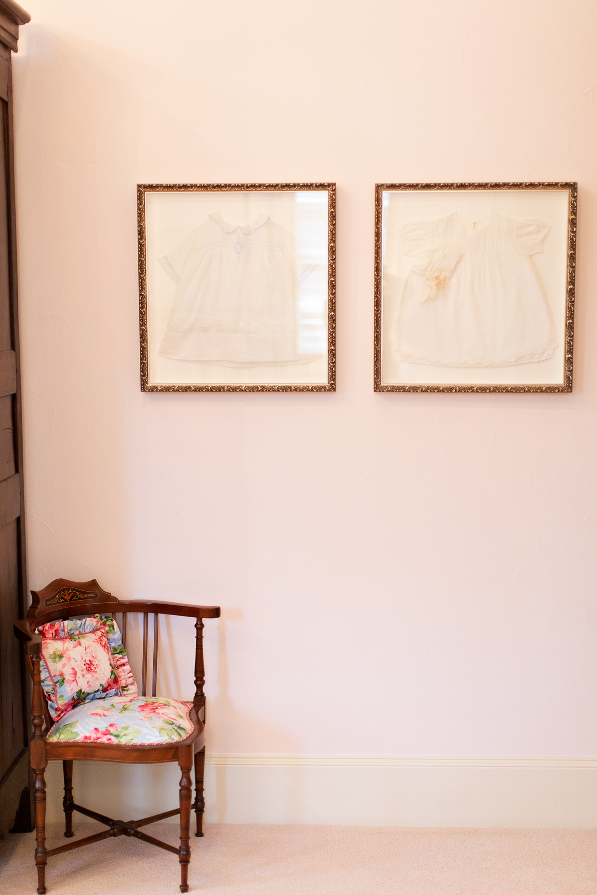 two framed baptismal gowns on the wall of a room