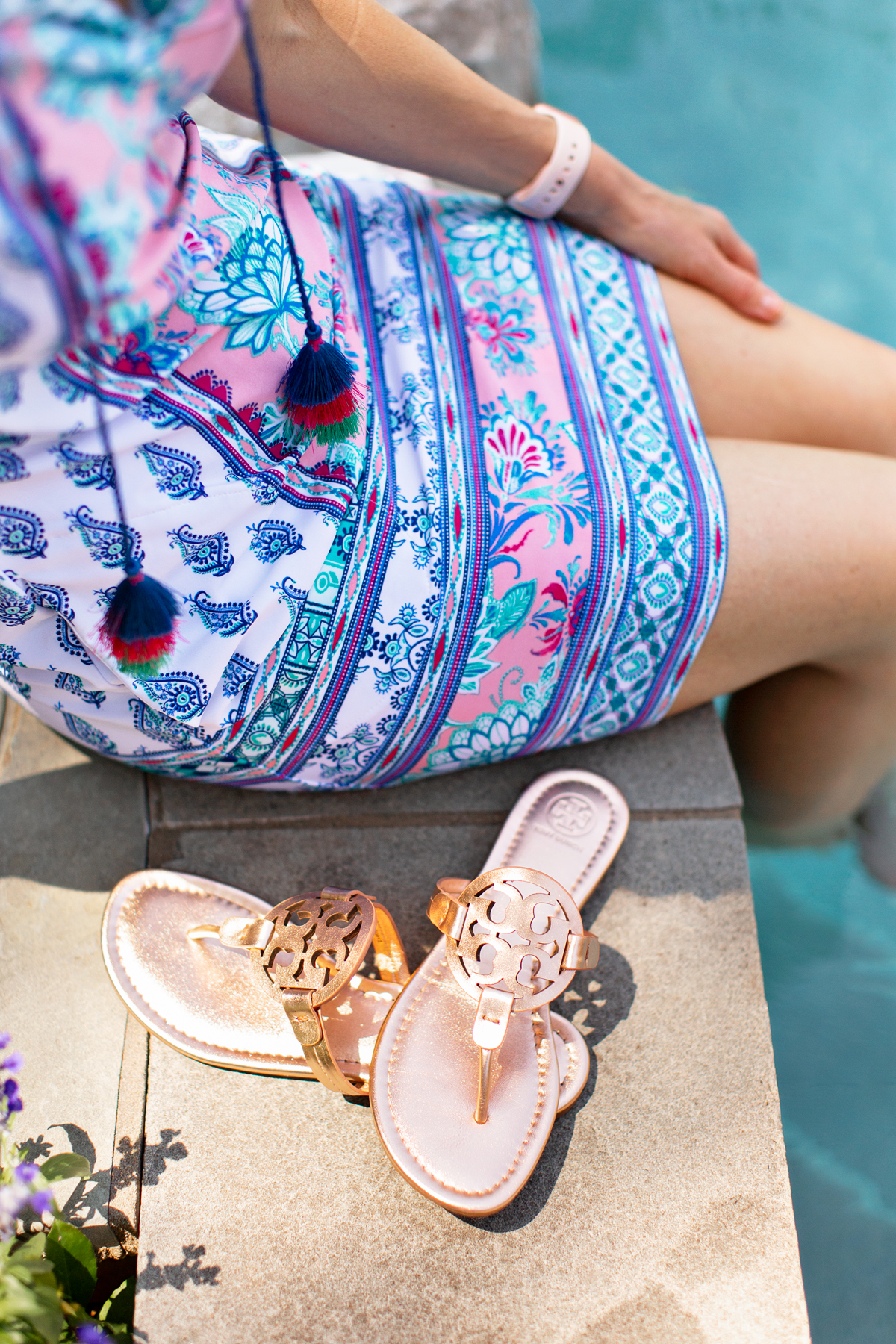 skirt of a woman's dress and tory burch rose gold miller sandals beside a pool