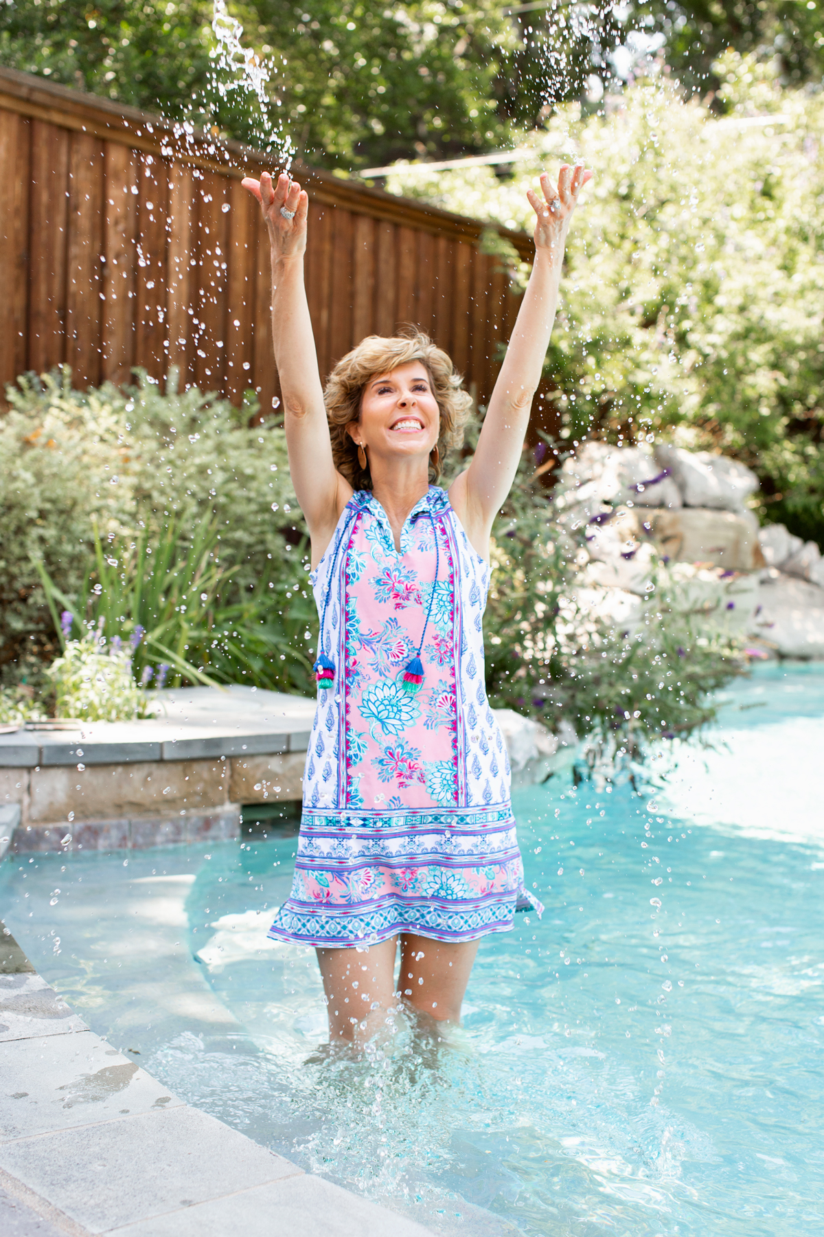 woman standing in a pool and throwing water into the air