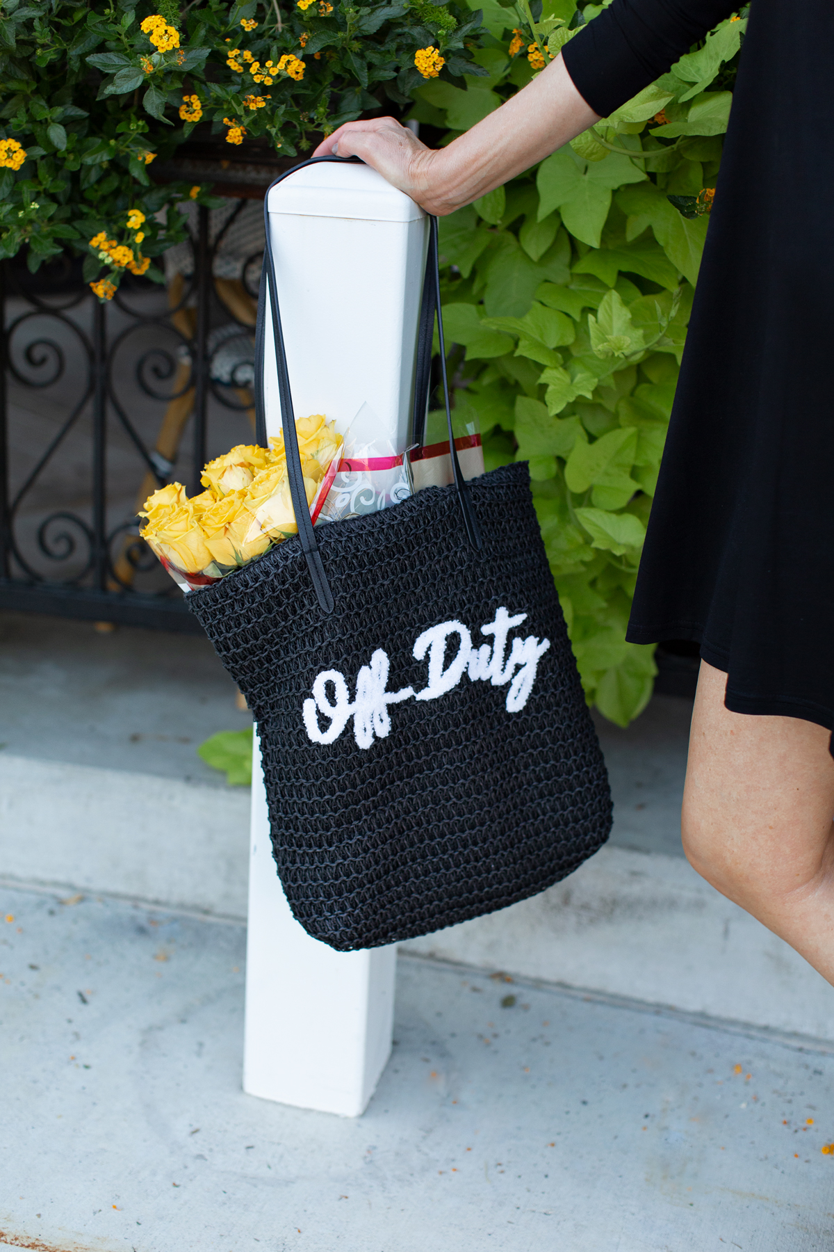 black raffia bag with off-duty on it in white letters