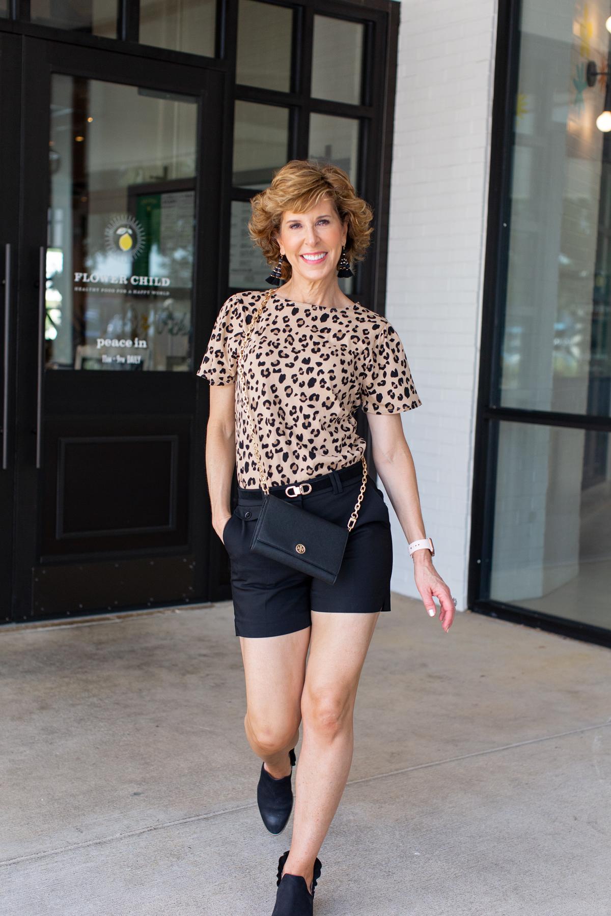 woman in leopard print top and black shorts walking toward camera