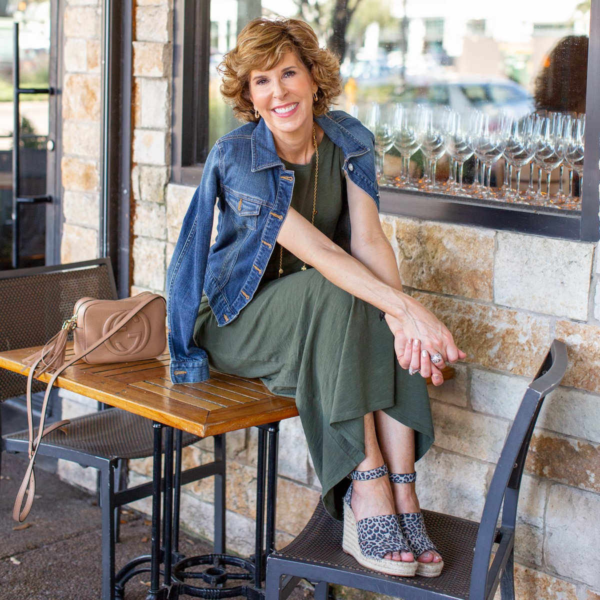 woman in green dress and denim jacket sitting on a restaurant patio table