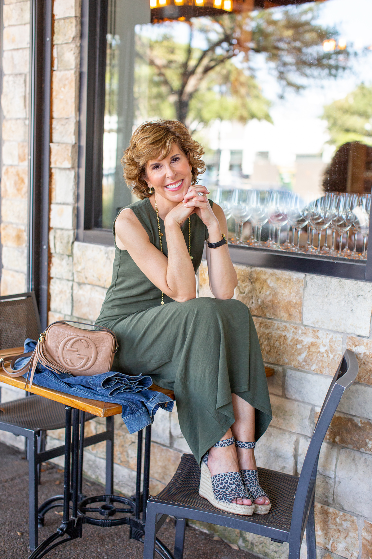 woman in green dress sitting on a restaurant patio table