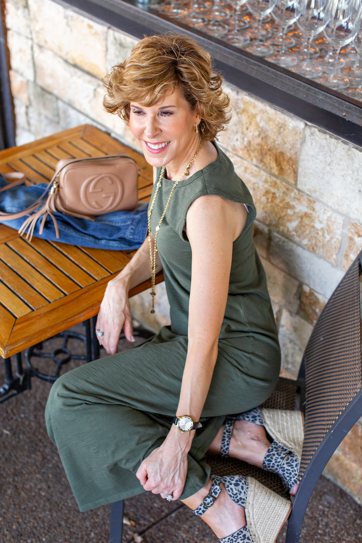woman in green dress sitting at a restaurant patio table
