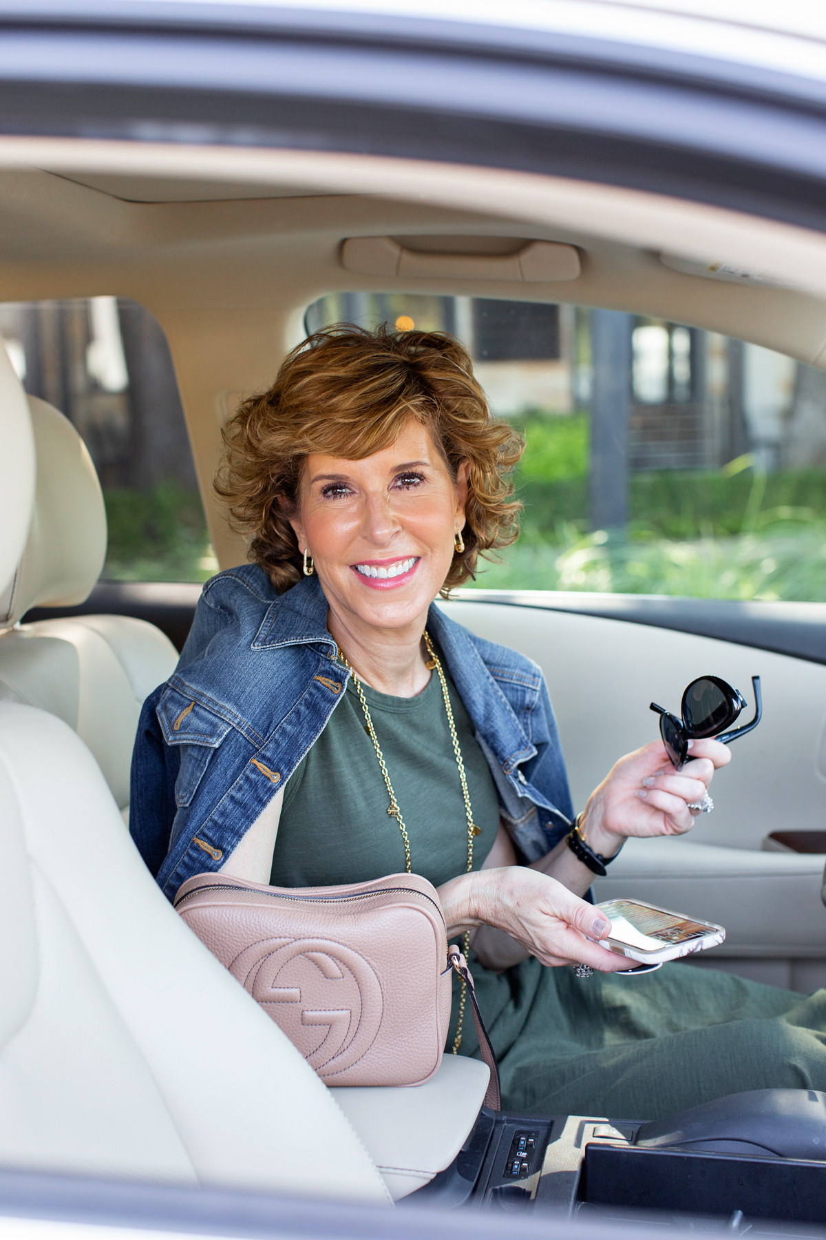 woman in green dress and denim jacket sitting in her car holding her phone looking at camera