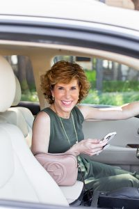 woman in green dress sitting in her car holding her phone looking at camera and reviewing the new rules for texting