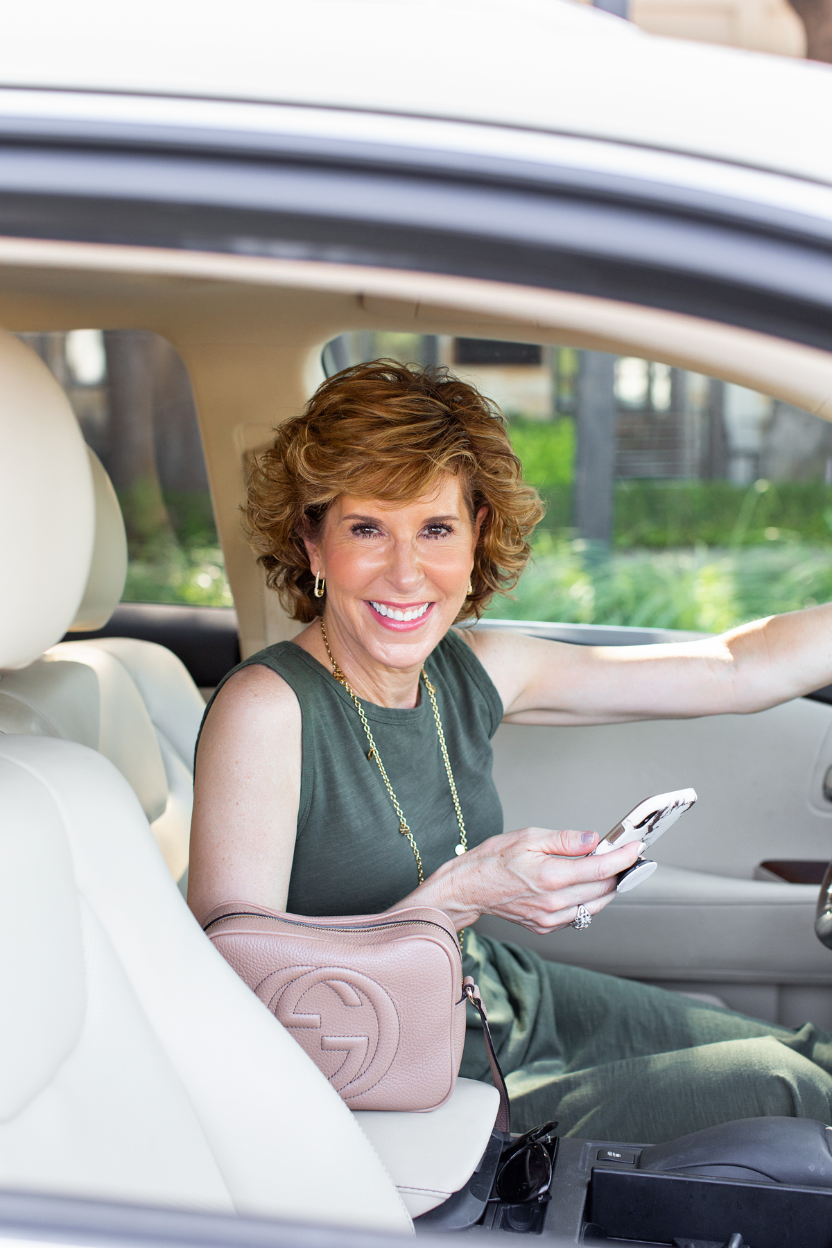 woman in green dress sitting in her car holding her phone looking at camera