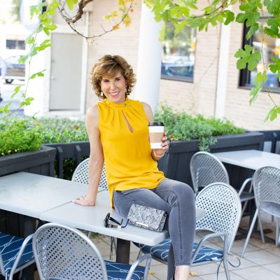 woman in yellow top sitting on table on restaurant patio holding a disposible coffee cup and having september's coffee talk