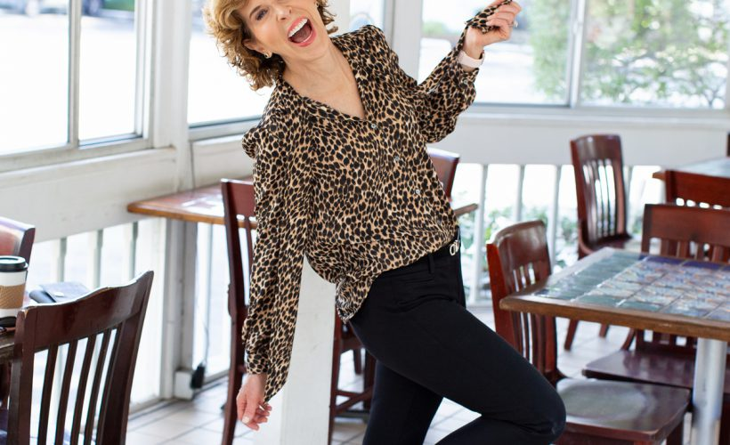 laughing woman standing on one foot wearing animal print tie neck blouse