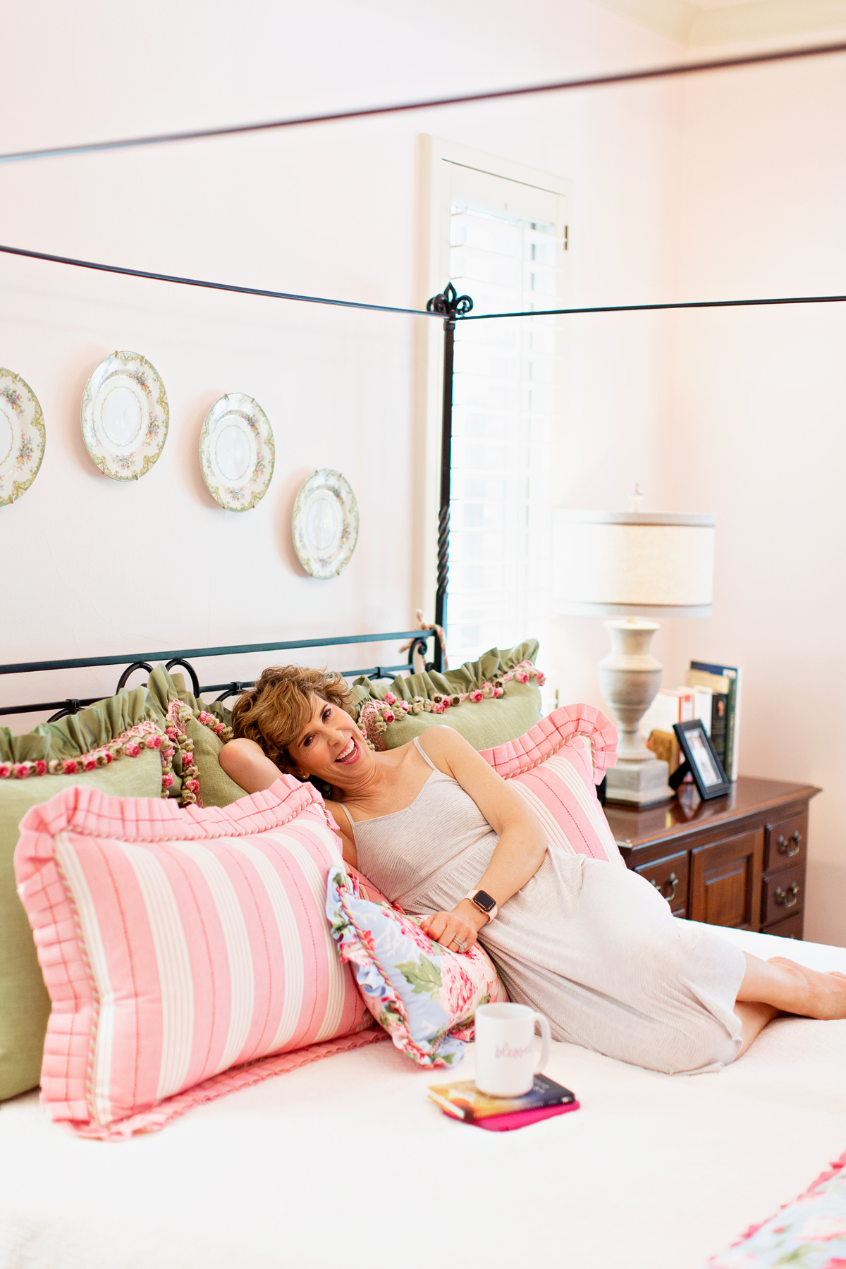 woman in nightgown on her bed with head on decorative pillows