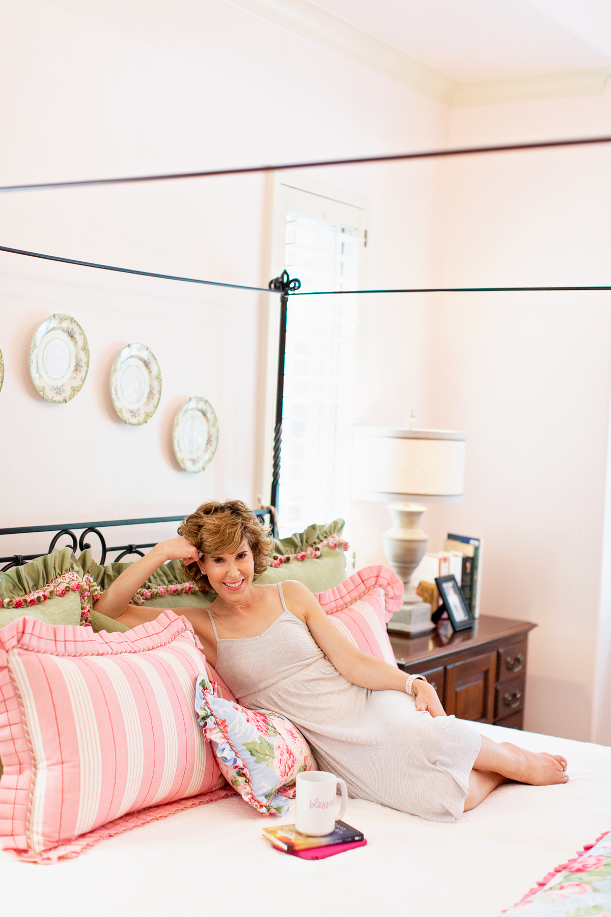 woman in nightgown on her bed looking at camera