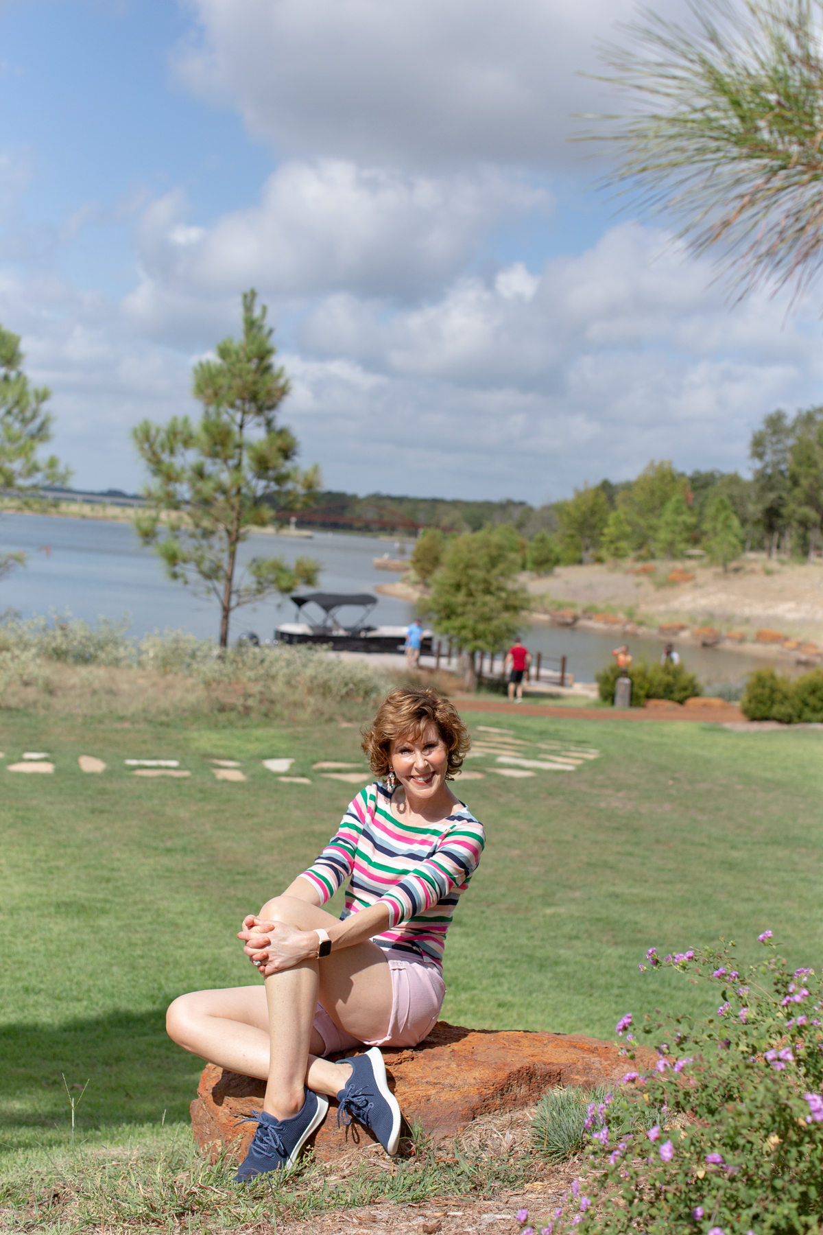 woman on a weekend getaway at long cove sitting on a rock with the lake in the background