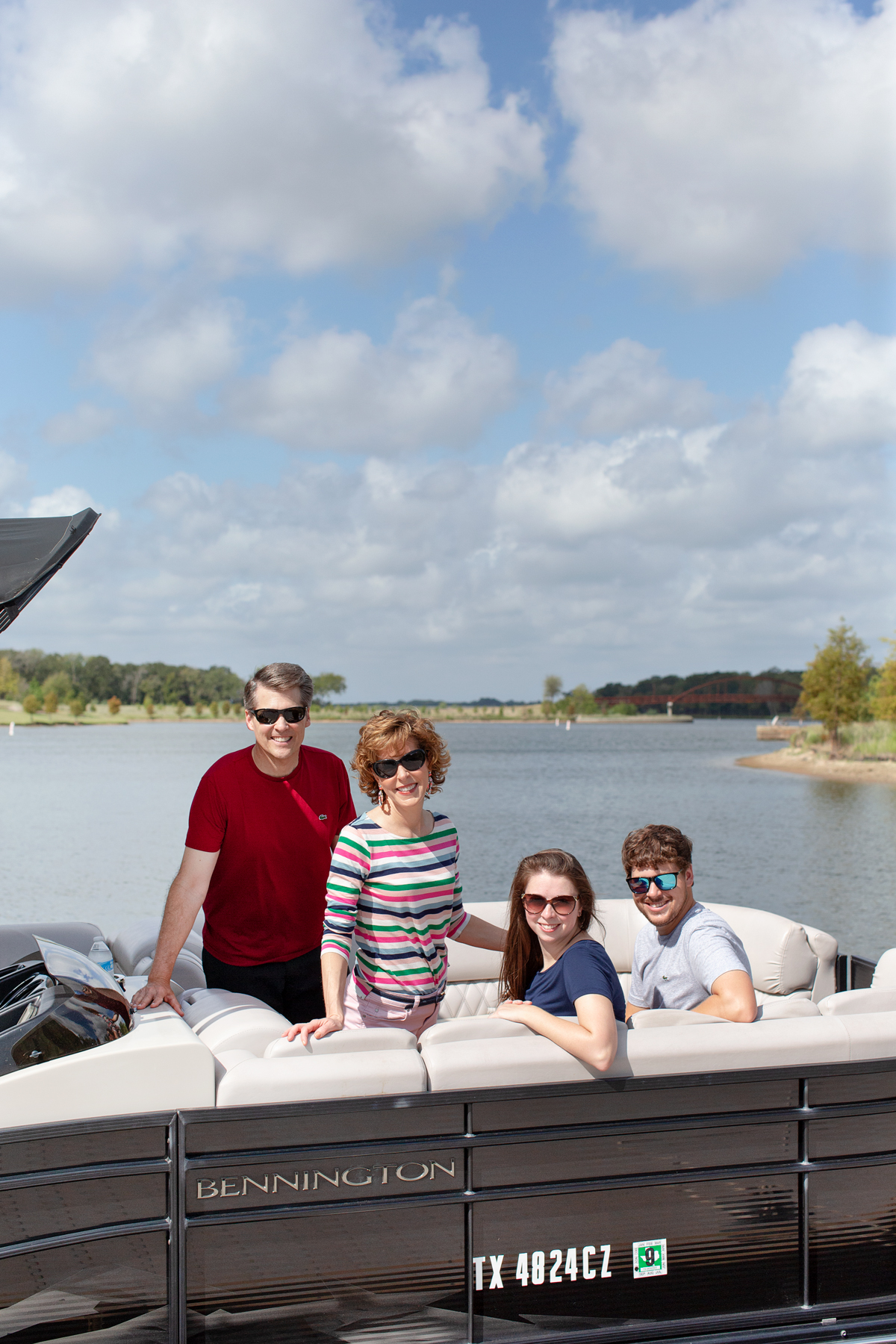 a family of four on a boat looking at camera with a lake behind them