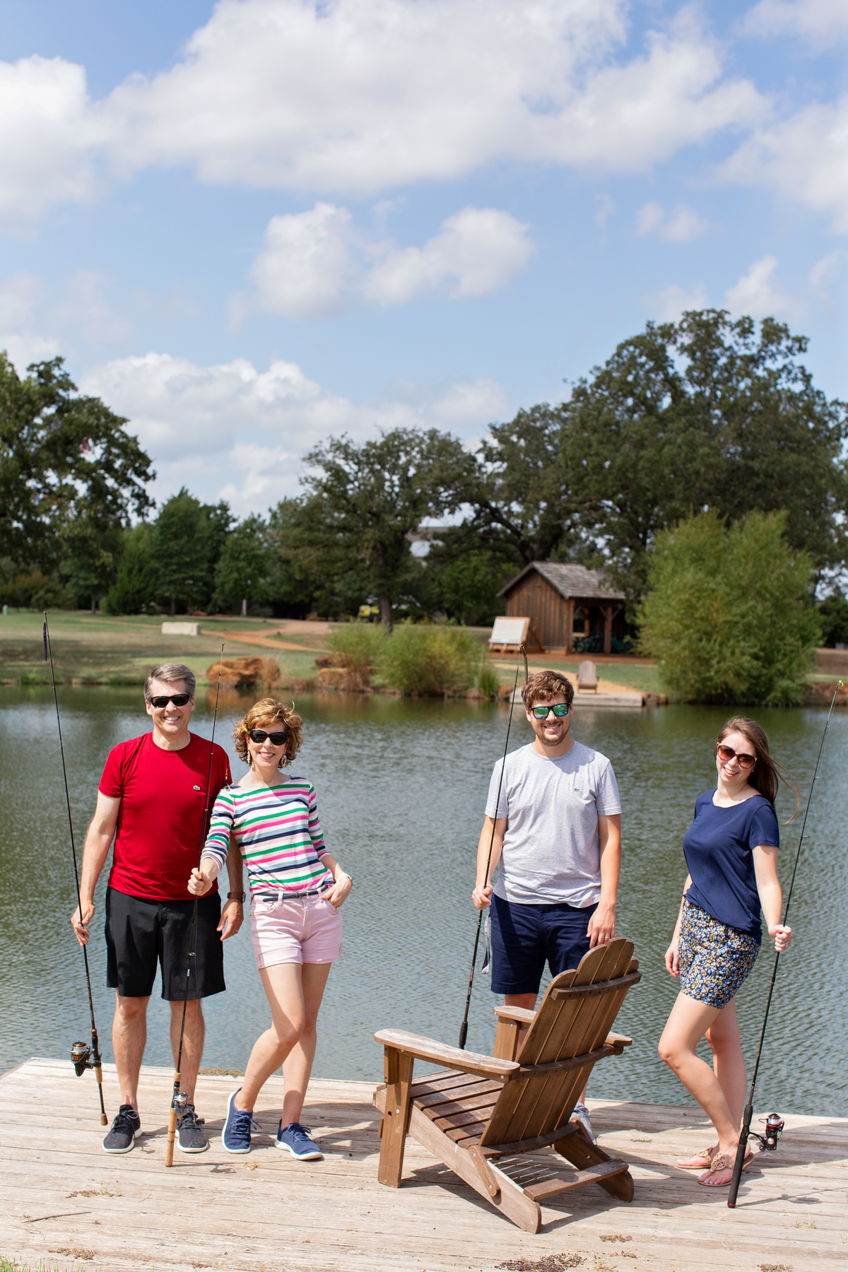 two couples posing with fishing poles in front of a lake on a weekend getaway at long cove
