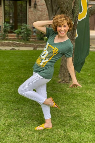 woman wearing baylor basketball JOY shirt and white jeans posing in her front yard by baylor flag