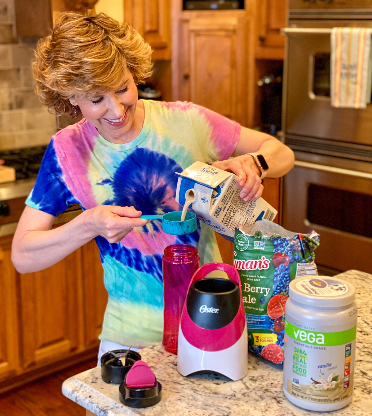 woman in tie dye shirt making a smoothie in kitchen