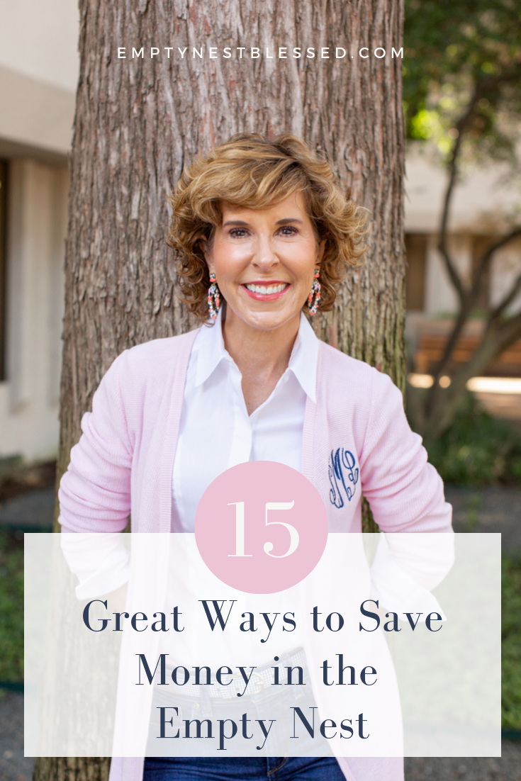 woman in pink monogram cardigan standing by a tree and looking at the camera with graphics saying 15 ways to save money in the empty nest
