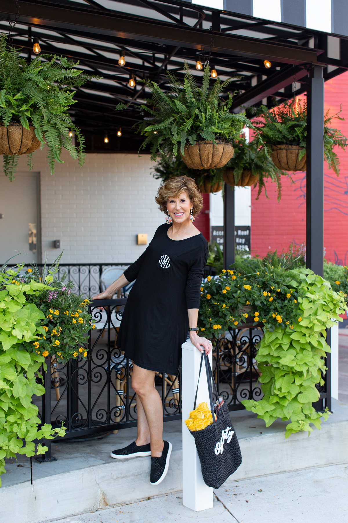 woman in black monogrammed dress by a restaurant patio