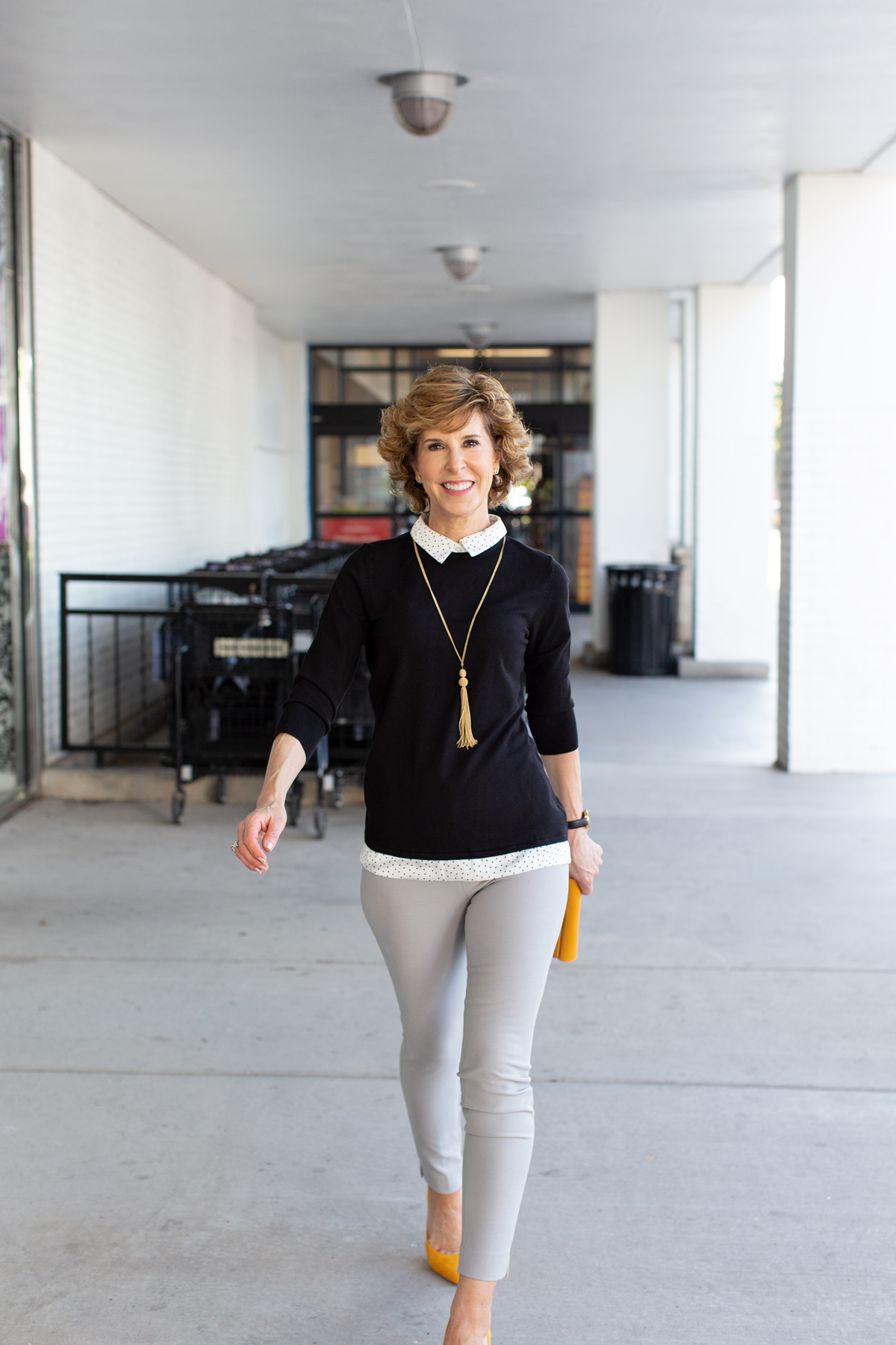 woman in black sweater with yellow shoes and purse walking towards the cameras