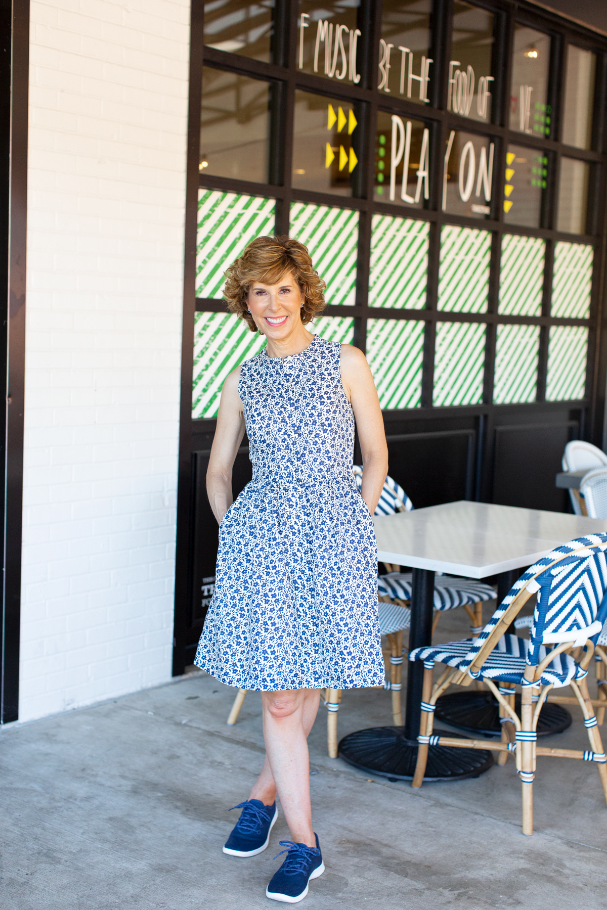 woman in blue floral dress on a restaurant patio