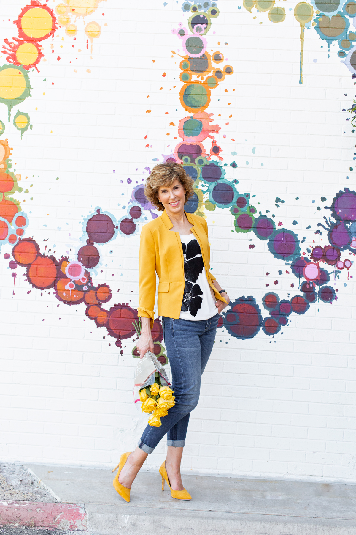 woman in gold blazer standing by a colorful peace sign painted wall thinking about what she learned this week