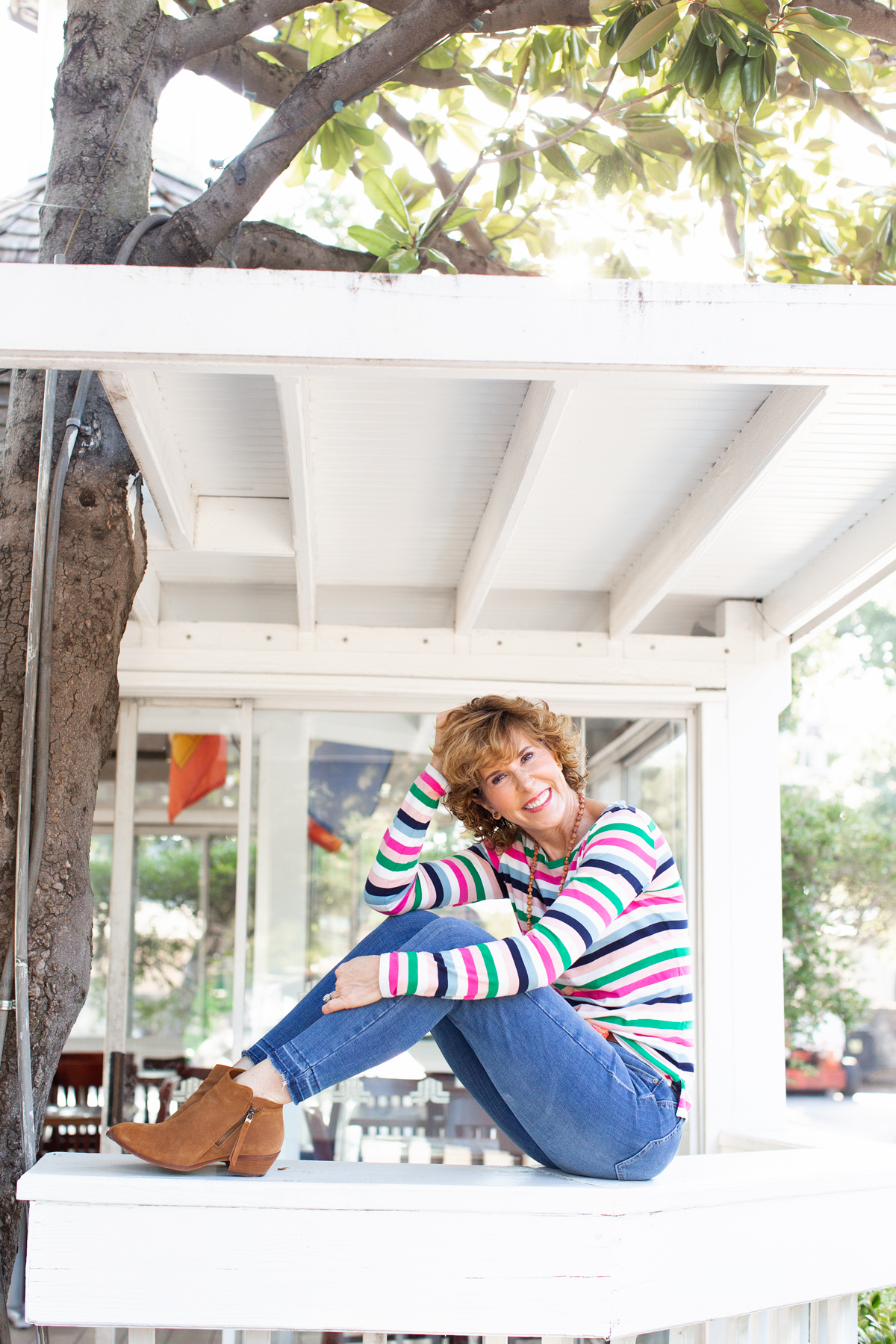 woman in striped top, jeans, and brown booties sitting on a white railing