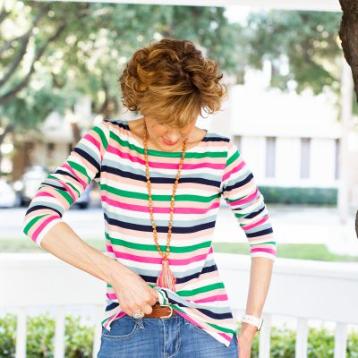 woman in striped top demonstrating how to do the half-tuck with her shirt