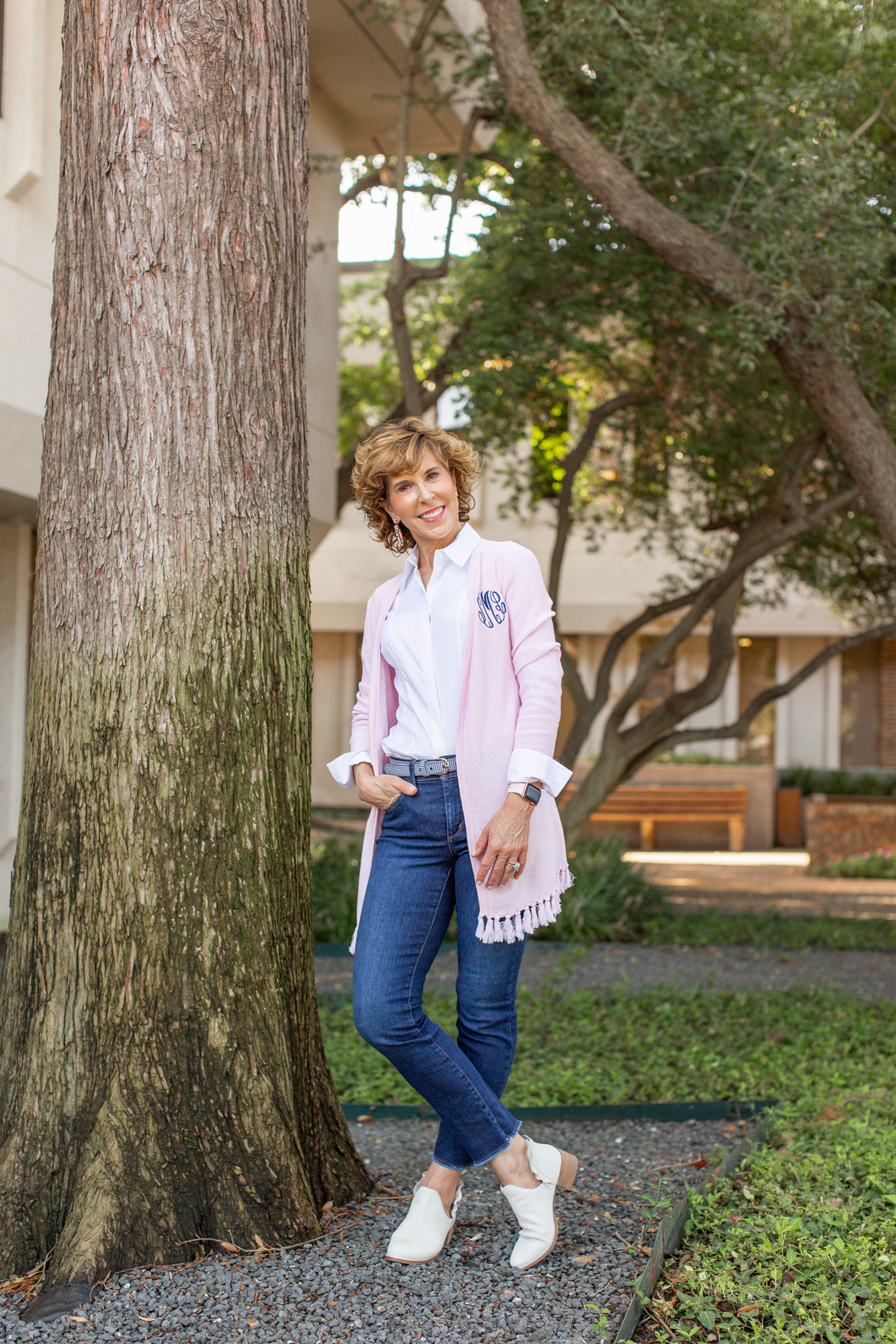 woman in pink cardigan with one hand in jeans pocket standing next to a tree trunk looking at the camera