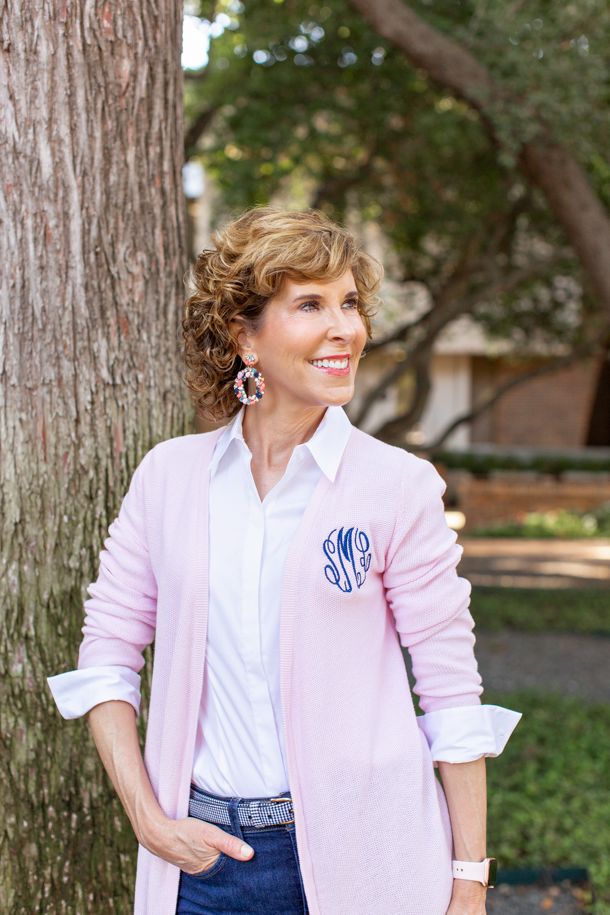woman in pink cardigan standing next to a tree trunk looking to the side