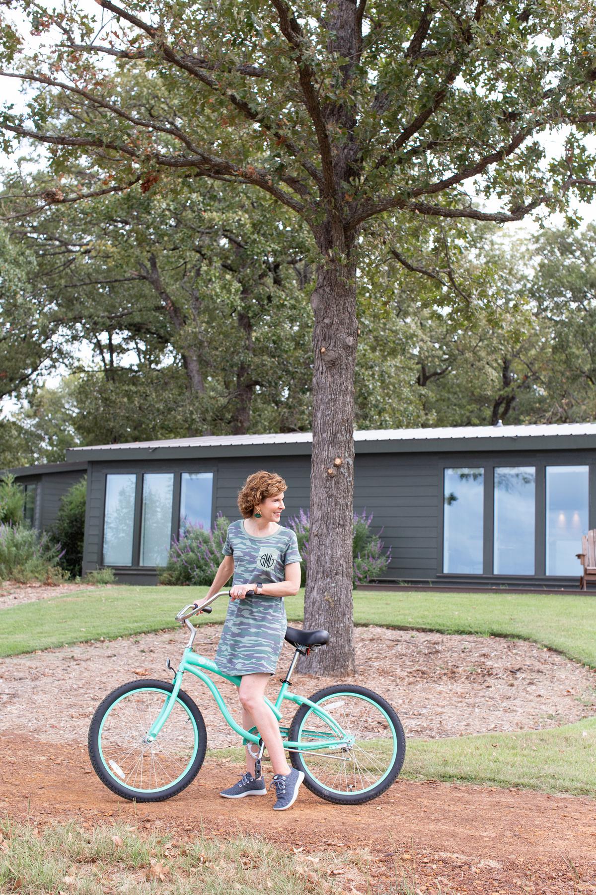 woman wearing camo dress riding a bike