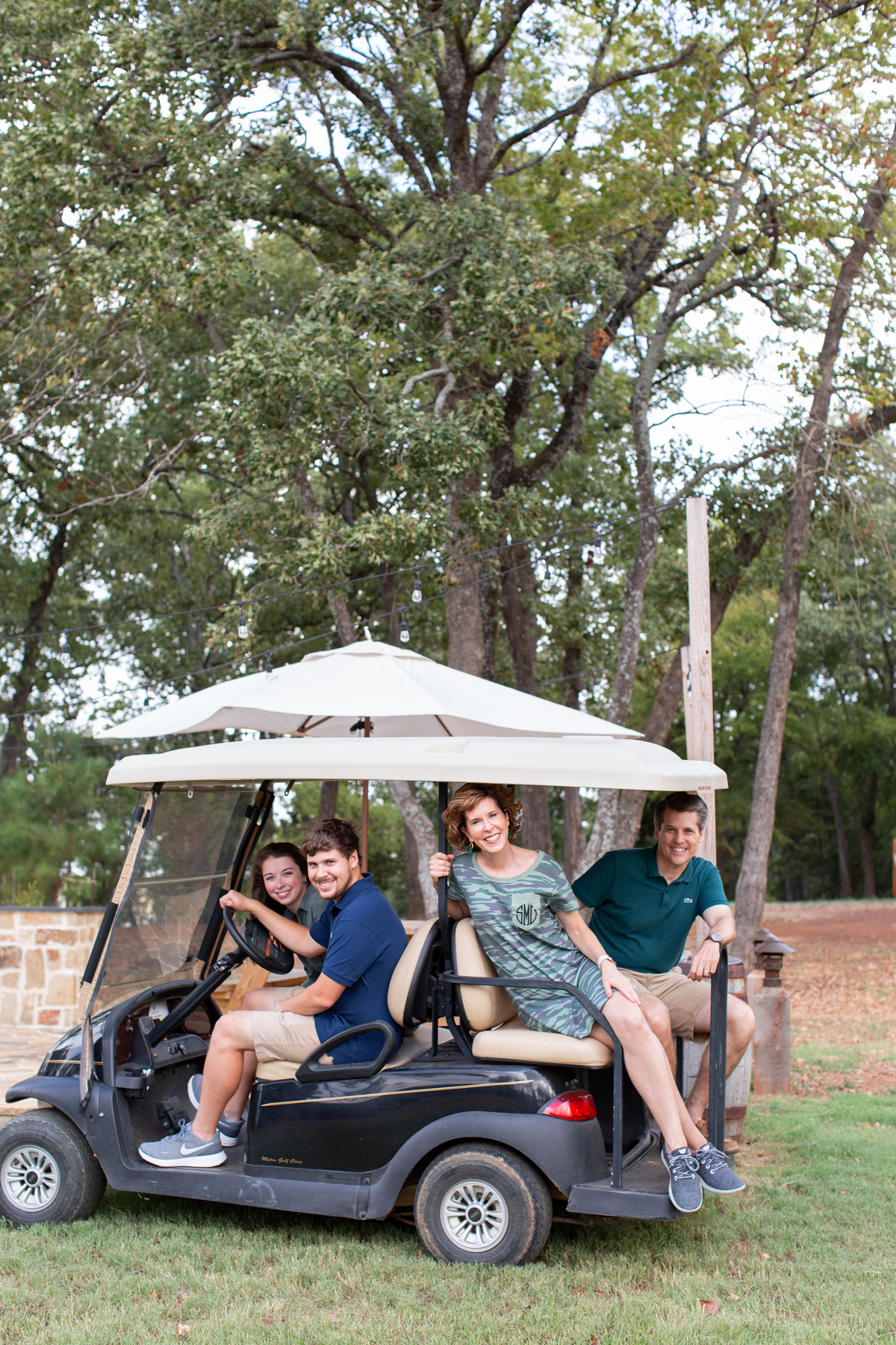 a family of four riding on a golf cart