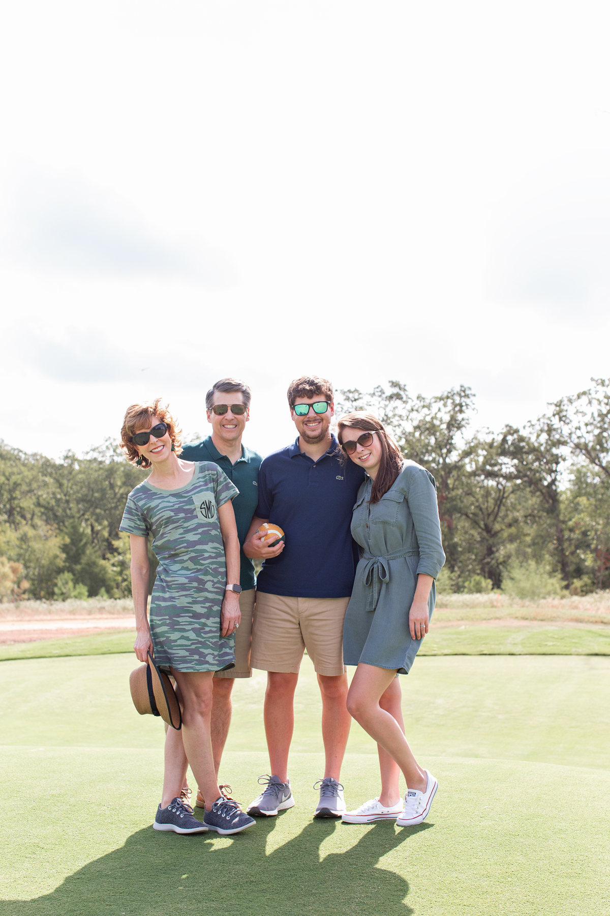 four adults posing and looking at the camera on the golf course at long cove