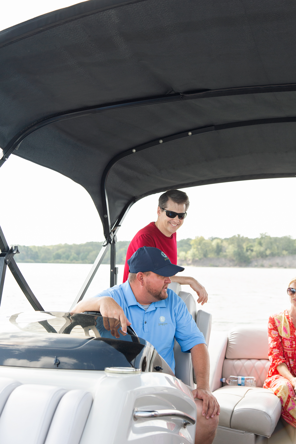 man in blue shirt driving a boat with a man in a red shirt standing behind him