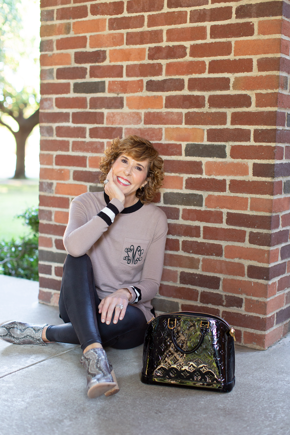 woman in tan monogrammed sweater sitting in front of a brick wall