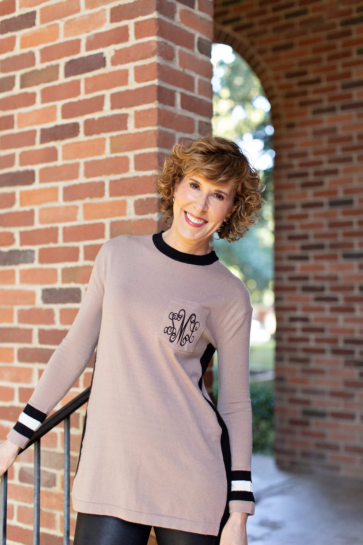 woman in tan monogrammed sweater standing in front of a brick wall