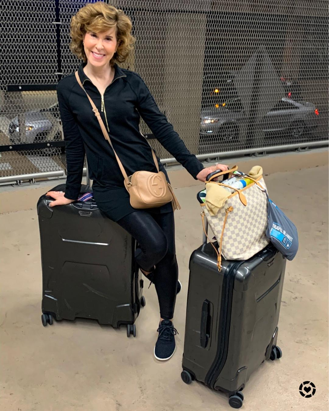 woman wearing black with suitcases at an airport