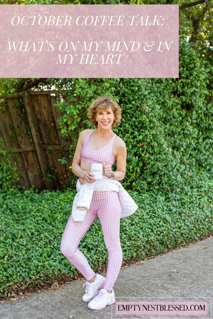 Woman in pink and white workout wear holding a coffee cup in front of a green wall with text graphics