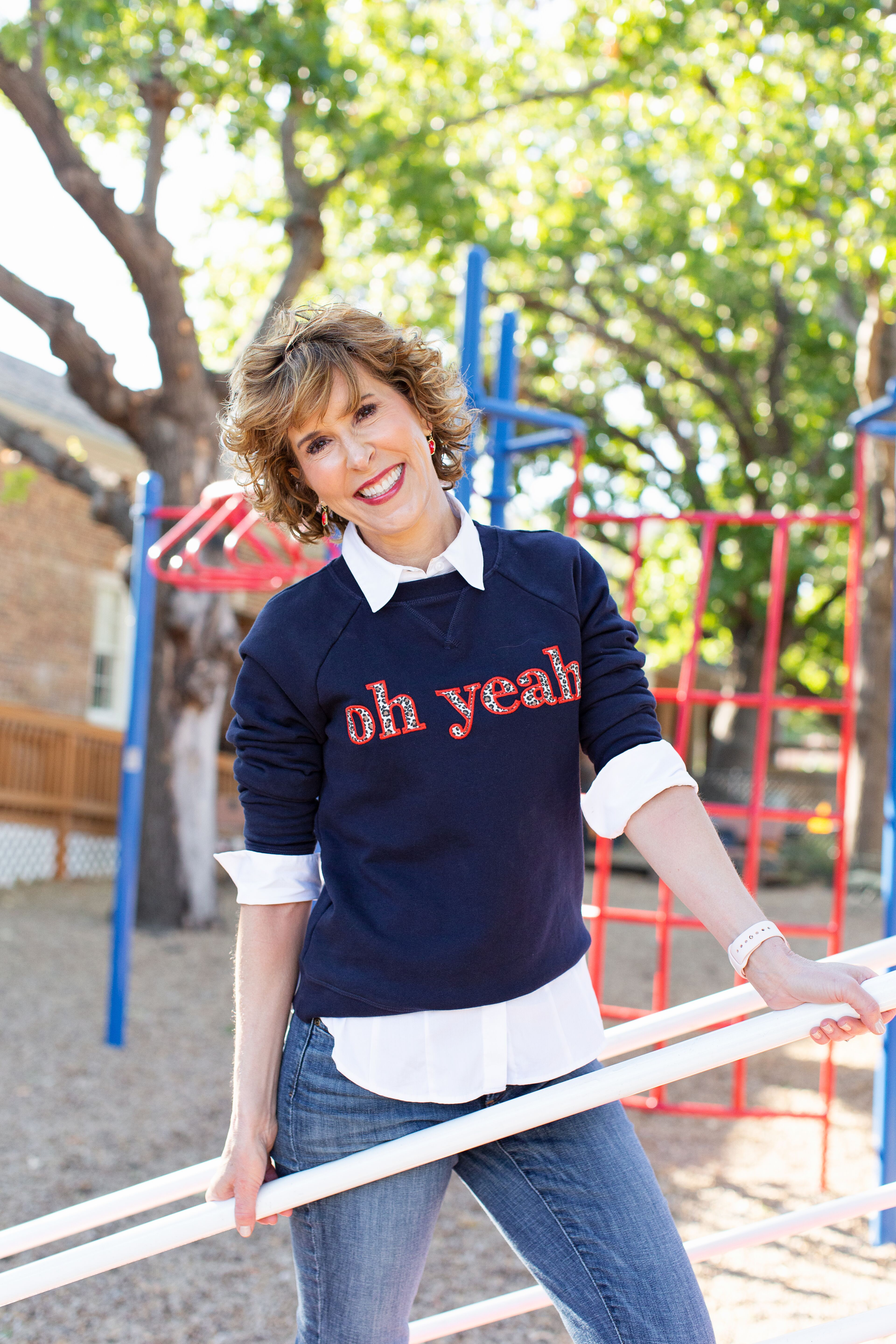 """woman wearing blue sweatshirt that says """"oh, yeah"""" in leopard print letters"""
